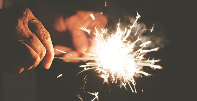 Older person holding a sparkler