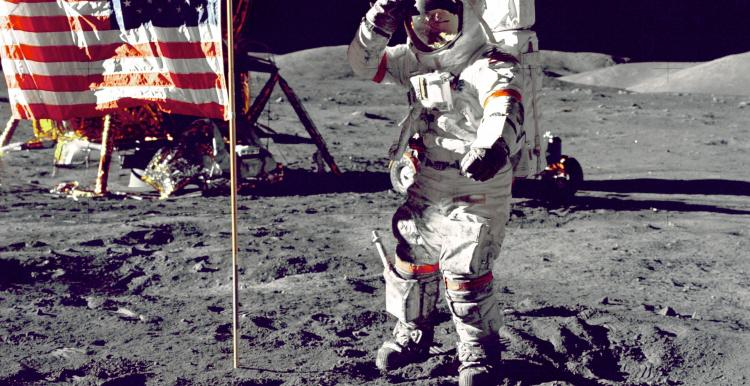 A snapshot from NASA when man took there first few steps on the moon. In the image shows one of the astronauts on the moon, next to the American flag.