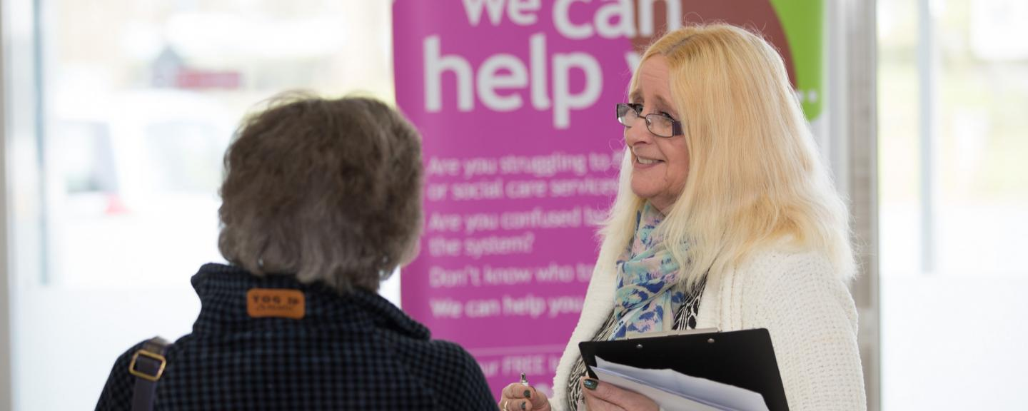 A Healthwatch member smiling at a lady who is talking to her.