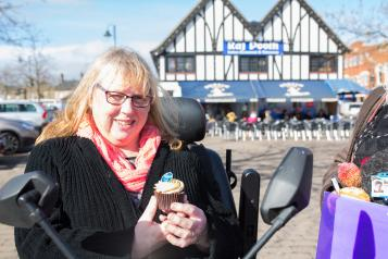 Woman in an electric wheelchair is holding a cupcake while outside.
