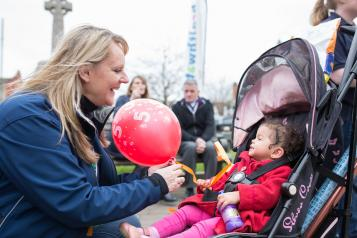 A volunteer handing a balloon over to a young child in a pram.