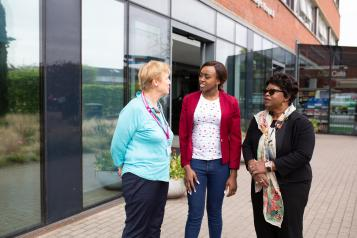 Three women standing outside a hospital talking