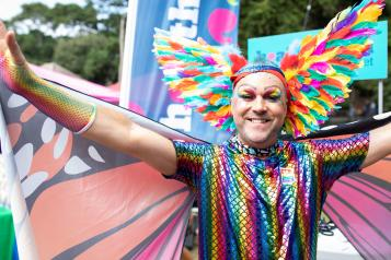 A person dressed as a rainbow butterfly, spreading their wings at a pride festival
