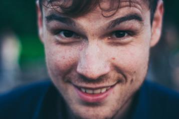 A close up of a brunette man smiling at the camera.