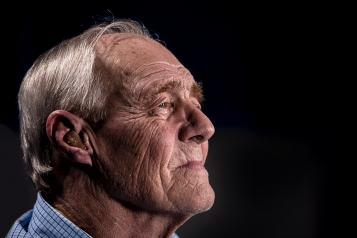 An older man sitting in front of a black background.