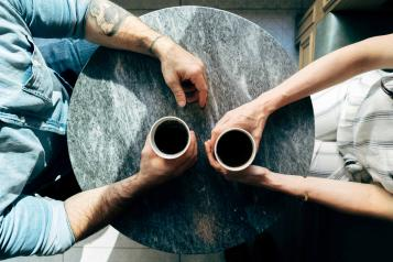 Two people sitting at a coffee table with there arms over the table.
