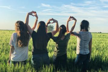 Four girls standing in a field using their hands to make hearts.