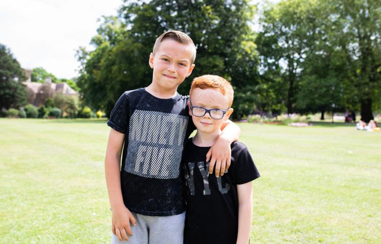 Two boys together, smiling at the camera